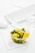 Kiwi fruit and pineapple salad in plastic container