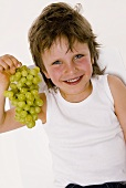 Small boy with a bunch of grapes in his hand