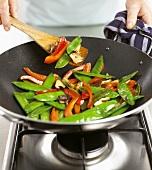 Sautéing vegetables in a wok