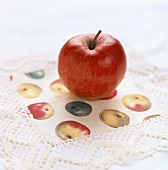 An apple on a doily with apple design