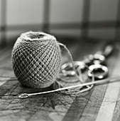 A ball of kitchen string with needle and scissors
