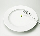 A pea on a plate with a fork