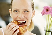 Smiling young woman biting into a lye croissant