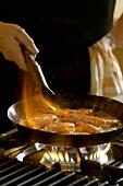 Flambéing lemon and garlic prawns