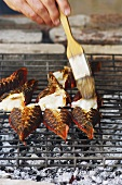 Spiny lobster tails on grill, being brushed with oil
