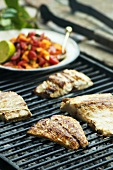 Fish fillets on barbecue with tomato and papaya salsa