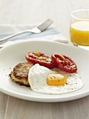 Fried egg with potato cake and fried tomato