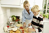 Woman with blond boy cutting a hamburger bun