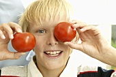 Blond boy with two tomatoes
