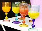 Orange juice in coloured glasses