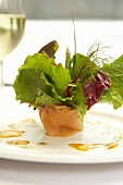 Salmon roll filled with salad leaves
