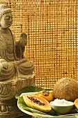 Buddha with exotic fruit and coconut