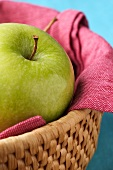 A Granny Smith apple in a small basket
