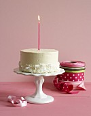 A cake with candle on a cake stand