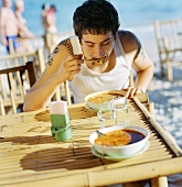 Young man eating seafood soup at a beach restaurant