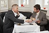 Zwei Männer bei Verhandlungen in einem Restaurant