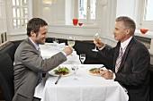 Zwei Männer mit Anzug sitzen im Restaurant beim Essen