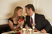 Young man giving woman gift over romantic dinner
