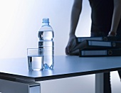 A glass of water and a bottle of water on desk