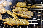 Chicken satay on a barbecue