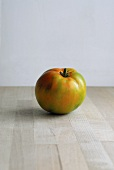 A green tomato on a wooden surface