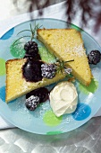Pieces of lemon cake with blackberries and whipped cream