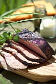 Slices of roast beef on a wooden table out of doors