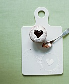 A cupcake with a jam heart on a chopping board