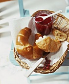 A jar of redcurrant and vanilla jam with croissants