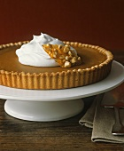Pumpkin pie with whipped cream on a pedestal cake stand