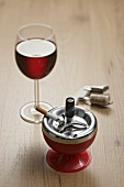 A glass of red wine with a cigarette in an ashtray