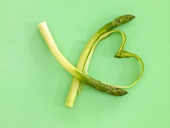 Two peeled spears of green asparagus, peelings forming a heart