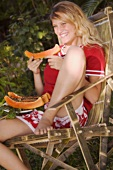 Girl eating papaya on a chair out of doors