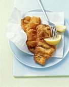 Wiener schnitzel with lemon wedges & paper on plate