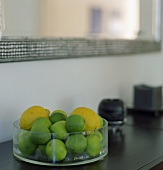 Limes and lemons in a glass bowl on a cabinet
