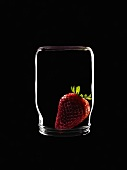 A strawberry in an upturned yoghurt jar