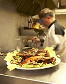 Whole crab on lettuce leaves, chef in background (Asia)