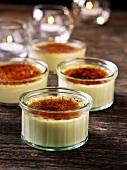 Four crème brûlées in glass ramekins with windlights
