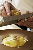 Man shaving white truffle onto pasta in butter sauce