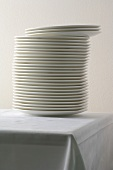A stack of porcelain plates on a table with a tablecloth
