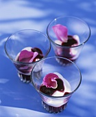 Three glasses of yoghurt with berry sauce and rose petals