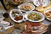 Gedeckter Tisch mit Antipasti und Rotwein, Toskana