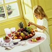 Little Girl Taking a Strawberry from a Fruit Bowl