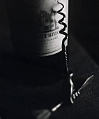 Bottle of 1967 Chateau Haut-Brion, corkscrew in front (b/w)