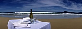 Table with White Wine and Dinnerware at the Beach