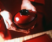 Hands holding a red soup bowl with a lid