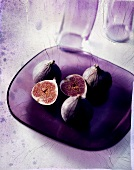 Whole and opened figs on glass plate
