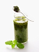 A Jar of Pesto with Spoon and Basil Leaf