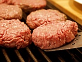 Several Hamburger Patties on the Grill with Spatula