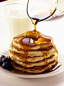 Pouring Maple Syrup Over a Stack of Pancakes